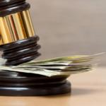 court gavel being slammed on top of money