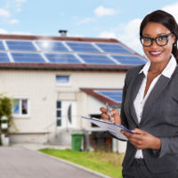 Businesswoman Filling Document In Front Of House