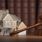 House with gavel and law books.  Real estate law and house auction concept